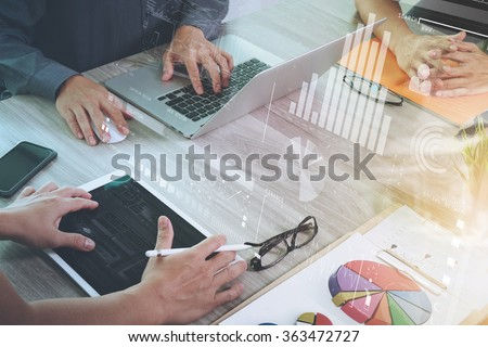 business documents on office table with smart phone and laptop computer and graph financial with social network diagram and three colleagues discussing data in the background - stock photo