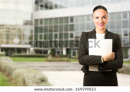 Business dressed woman with folder, standing in front of the building. - stock photo
