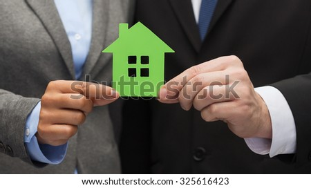 business, eco and real estate concept - businessman and businesswoman holding green house - stock photo
