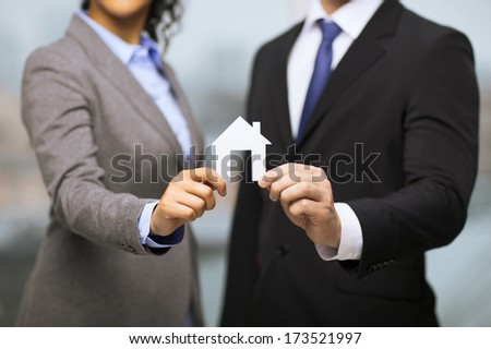 business, eco, real estate and office concept - businessman and businesswoman holding white paper house in office - stock photo