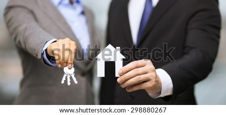 business, eco, real estate and office concept - businessman and businesswoman holding white paper house and keys in office - stock photo