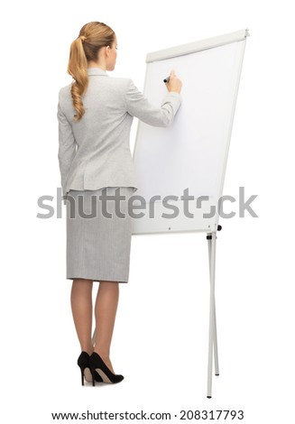 business, education and office concept - businesswoman or teacher with marker writing or drawing something imaginary on whiteboard from back - stock photo