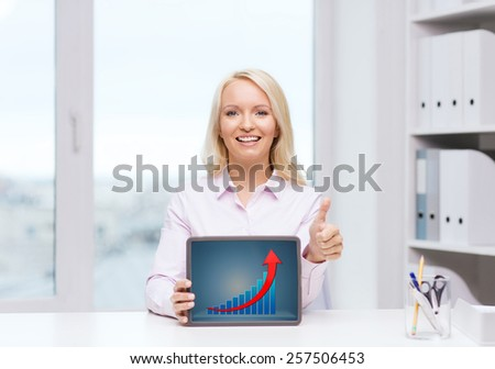 business, education, gesture and technology concept - smiling businesswoman showing thumbs up and tablet pc computer screen with growing graph in office - stock photo
