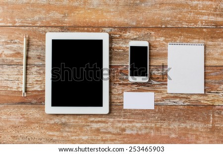 business, education, objects and technology concept - close up of notebook, tablet pc computer and smartphone on table - stock photo