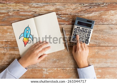 business, education, people and technology concept - close up of female hands with calculator, pen and rocket drawing in notebook on table - stock photo