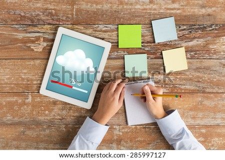 business, education, people and technology concept - close up of female hands writing to notebook with tablet pc computer transferring data - stock photo