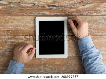 business, education, people and technology concept - close up of male hands with tablet pc computer on table - stock photo
