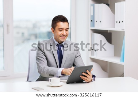 business, education, people and technology concept - smiling businessman with tablet pc computer and coffee in office - stock photo