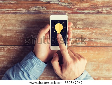 business, education, people, inspiration and technology concept - close up of male hands holding smartphone and pointing finger to screen with light bulb icon on table - stock photo