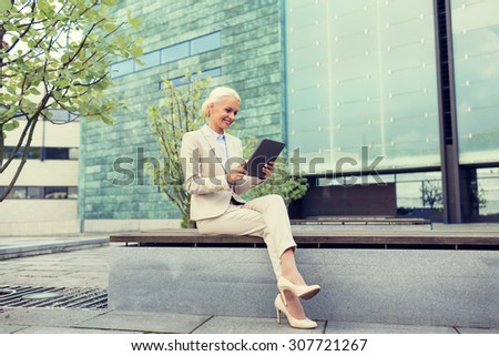 business, education, technology and people concept - smiling businesswoman working with tablet pc computer on city street - stock photo