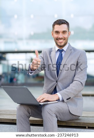 business, education, technology, gesture and people concept - smiling businessman working with laptop computer showing thumbs up on city street - stock photo