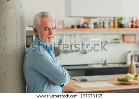 Business elderly man in his kitchen - stock photo