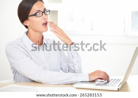 Business employee with glasses looking shocked while working on her computer and looking at you - stock photo