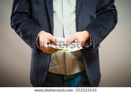 Business executive in formal suit giving money as a bribe - stock photo