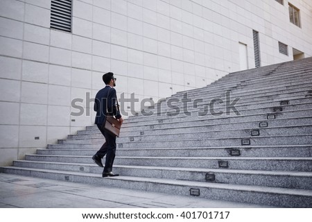 Business executive with briefcase going up the stairs - stock photo