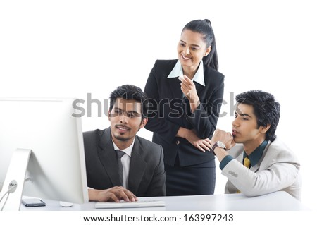 Business executives working on a desktop pc - stock photo