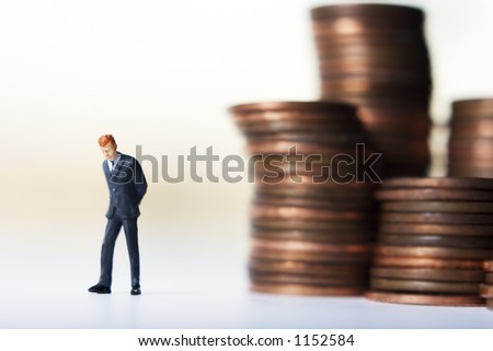 Business figure and stacks of coins - stock photo