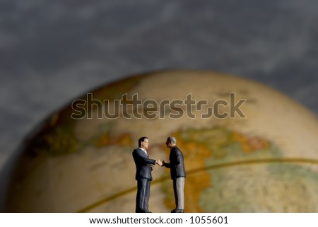 Business Figurines and Globe - stock photo