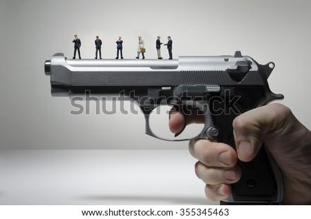 business figurines on a handgun  - stock photo