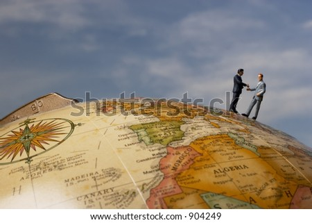 Business figurines on earth globe shaking hands with clouds - stock photo