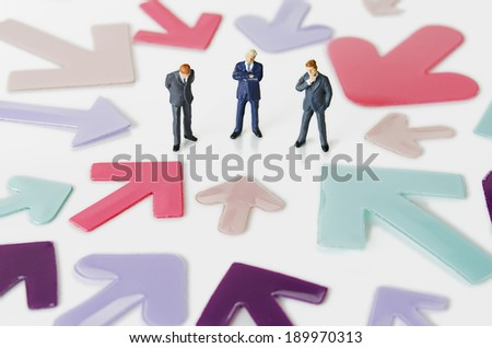 Business figurines with arrows - stock photo