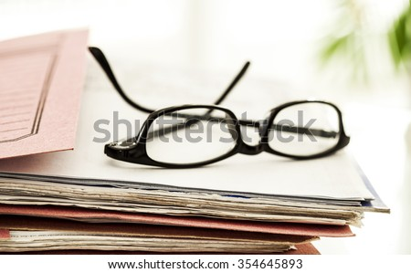 Business file and eyeglasses - stock photo