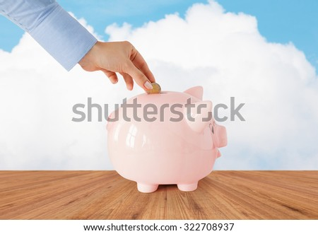 business, finance, investment, money saving and budget concept - close up of hand putting coin into piggy bank over blue sky and wooden floor background - stock photo