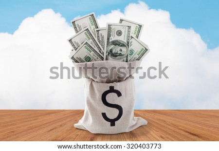 business, finance, investment, saving and cash concept - close up of dollar paper money in bag over wooden floor and blue sky background - stock photo