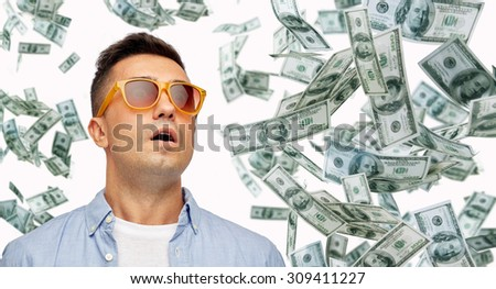 business, finance, luck, fortune and people concept - face of scared or surprised middle aged latin man in sunglasses with heap of falling dollar money - stock photo
