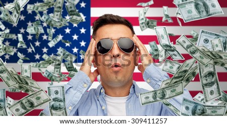business, finance, luck, fortune and people concept - face of scared or surprised middle aged latin man in sunglasses over american flag background with heap of falling dollar money - stock photo