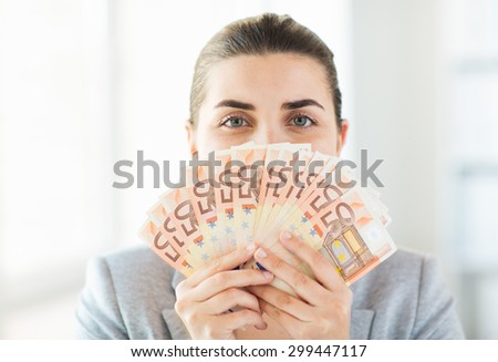 business, finance, saving, banking and people concept - close up of woman hiding her face behind euro money fan - stock photo
