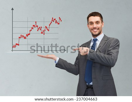 business, finances, economics, and people concept - smiling young businessman pointing finger and showing forex chart on palm of his hand over gray background - stock photo