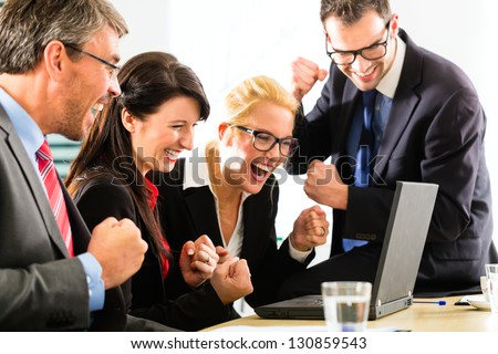Business - Four professionals in office in business attire looking at laptop screen working together, they rejoice - stock photo