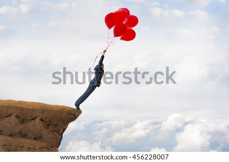 business freedom concept courageous daring businessman flying off a cliff holding faith in balloons - stock photo