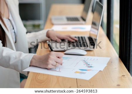 Business Girl analyzing investment charts with laptop. - stock photo