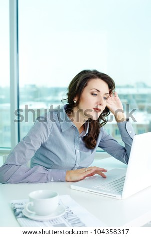 Business girl looking pensively at the laptop screen - stock photo