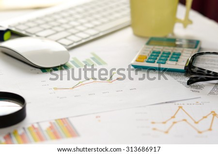business graph and laptop on the desk. - stock photo