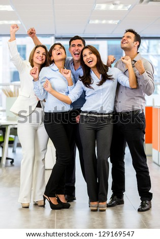 Business group with arms up celebrating their success - stock photo