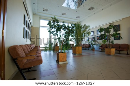business hall interior with plants armchairs and window - stock photo