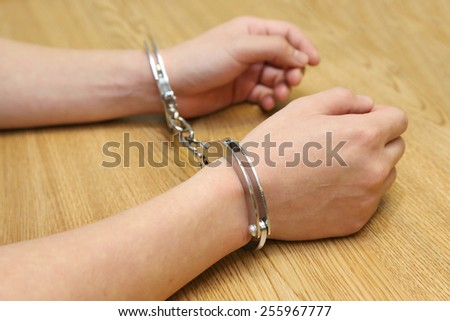 business hand arrested with handcuffs on the wooden table - stock photo