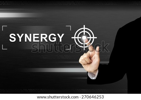 business hand clicking synergy button on a touch screen interface - stock photo