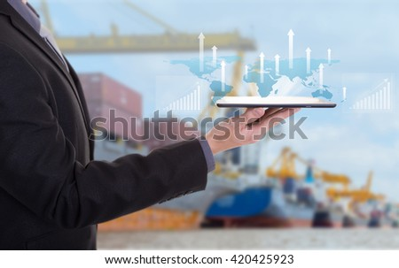 Business hand hold tablet with digital layer effect as business target concept,Industrial Container Cargo freight ship for Logistic Import Export background (Elements of this image furnished by NASA) - stock photo