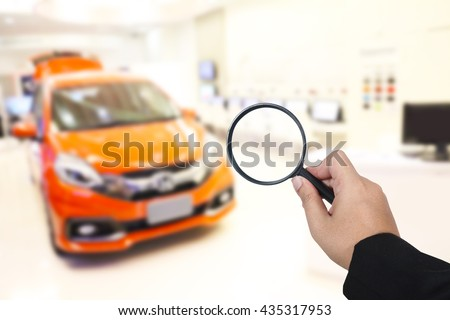 Business hand holding magnification find a new car - stock photo