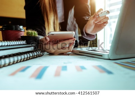 Business hand working and smart phone and laptop and graph business with social network diagramon office desk in office with morning light - stock photo