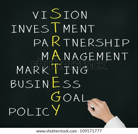 business hand writing strategy concept by crossword of vision, investment, partnership, management, marketing, goal, and policy - stock photo