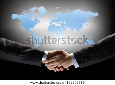 business handshake against black background with map image - stock photo