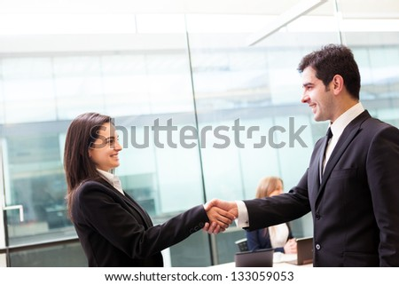 Business handshake at modern office with bussiness people on background - stock photo