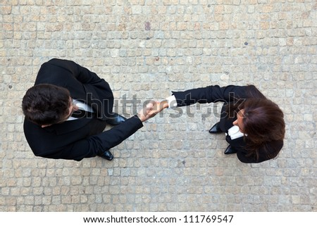 Business handshake between businessman and businesswoman - stock photo