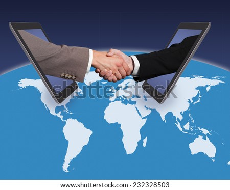 Business handshake emerging from digital tablets on world map against blue background.  - stock photo