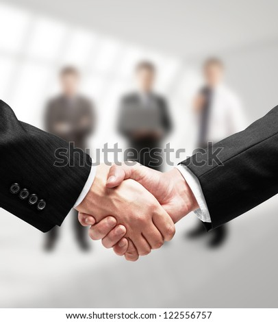 business handshake in gray room - stock photo